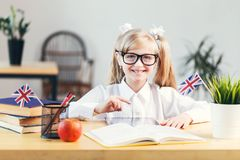 Studying in Classroom. Happy smiling girl wears white shirt and eyeglasses learning English language with book in light stylish classroom, studying success stock images