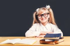 Studying in Classroom. Portrait of cute young girl wears smart eyeglasses learning English language with book before dark background royalty free stock image