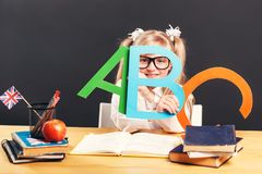 Studying in Classroom. Young pupil girl wears smart eyeglasses holding colorful letters while learning English language with book before dark background royalty free stock photos