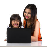 Studying with computer. A big sister helping her little sister doing homework on computer stock images