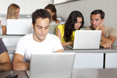 Studying with computer in class room Stock Images