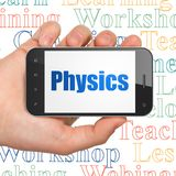 Studying concept: Hand Holding Smartphone with Physics on display. Studying concept: Hand Holding Smartphone with  blue text Physics on display,  Tag Cloud Royalty Free Stock Image