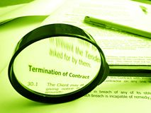 Studying conditions of a contract. A conceptual image of a magnifier focused on the words Termination of contract in a document listing the conditions of the Royalty Free Stock Photography