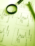 Studying electrical circuits plans. A conceptual photograph of a magnifying glass and pen placed over a detailed circuit plans used by engineers and architects Royalty Free Stock Image