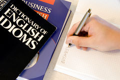 Studying English idioms. English idioms and business book, a hand holding a pen, writing in a notebook Stock Image