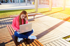 Studying for exam on park bench with open netbook and big copy space for text Royalty Free Stock Images