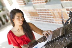 Studying female student on a laptop. A beautiful female student using a laptop and studying outdoors Stock Photos