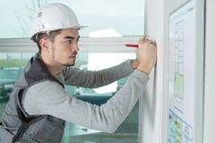 Studying the floor plan. Work stock image