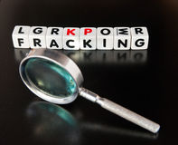 Studying fracking. Text ' fracking ' in uppercase black letters on small white cubes placed next to a hand magnifier , dark reflecting surface Royalty Free Stock Photography