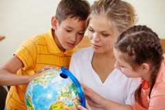 Studying geography. Portrait of cute classmates and teacher looking at globe at geography lesson royalty free stock photo