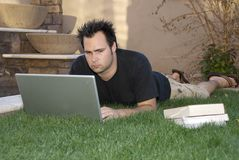 Studying in the grass. Young man with notebook computer and books laying in the grass studying Stock Photography
