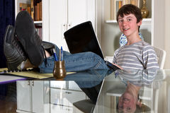 Studying at home. Young teenager kid studying with his laptop at home Stock Image