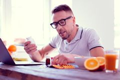 Bearded man feeling curious while studying the ingredients of food supplements. Studying the ingredients. Bearded man sitting on healthy diet feeling curious stock image
