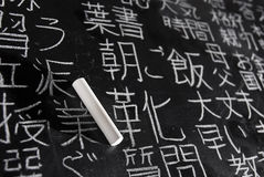 Studying Japanese. Chalk on blackboard filled with Chinese and Japanese characters. The words in Japanese have random meanings Royalty Free Stock Photo