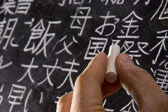 Studying Japanese. Close up of male hand writing Chinese and Japanese characters on blackboard. The words in Japanese have random meanings Stock Photography