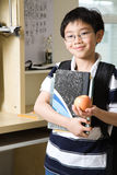 Studying kid with an apple. A shot of an asian kid studying at home holding an apple Stock Images