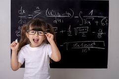 Studying kid. Pupil with glasses near black blackboard with formulas. Studying kid. Pupil with glasses near black blackboard. Studio shoot, Cute kid back to royalty free stock images