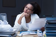 Studying late hours. Beautiful female student studying late hours at home royalty free stock photography