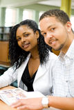 Studying in library. Two young attractive college students studying in the library Royalty Free Stock Image