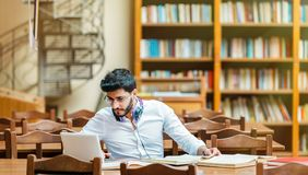 Studying in the Library. Concentrated bearded man studying with books and laptop in the university library Royalty Free Stock Photos
