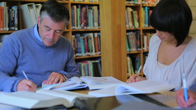 Studying in the library. Man studying in library with others stock video