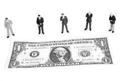 Studying the market. Managers studying the market around a dollar bill Royalty Free Stock Images