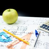 Studying math, back to school composition. Studying math back to school composition of the green apple and some stationery office supplies lying over the sheet Stock Photos