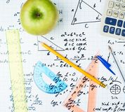 Studying math, back to school composition. Studying math back to school composition of the green apple and some stationery office supplies lying over the sheet Stock Photo