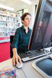 Studying online on a Computer at Library Stock Image