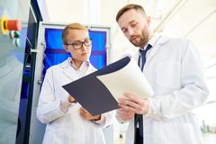 Studying Operation Manual. Pretty blonde-haired technician and her bearded colleague studying operation manual of modern equipment while standing at production Royalty Free Stock Photography