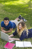 Studying outdoors together. Two students studying outdoors on a field of grass Stock Photos