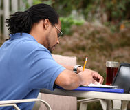 Studying Outside. Close up of young college student outside enjoying the weather while preparing himself for a test Stock Image