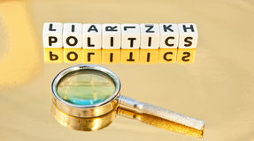 Studying politics. Text 'politics' inscribed in black uppercase letters on small white cubes placed on a reflective surface together with a hand magnifier Royalty Free Stock Photos