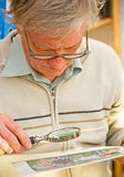 Studying a printed image. An image of a senior examining a printed image using a magnifier Royalty Free Stock Photos