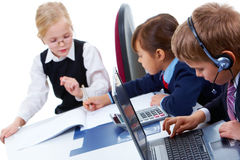 Studying process. Photo of serious lad with headset typing on background of communicating girls Stock Images