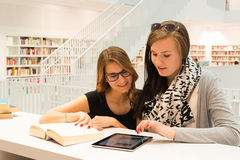 Studying at the public library. Two attractive female students are stuyding at the public library using a digital tablet and books Royalty Free Stock Image
