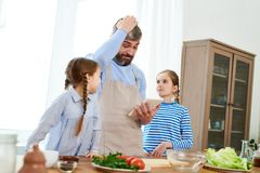 Studying Recipe on Digital Tablet. Puzzled middle-aged men wearing apron studying recipe of starter with help of digital tablet while his little daughters Royalty Free Stock Photos