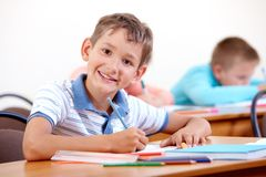 Studying at school. Portrait of smart lad looking at camera with classmates on background Stock Image