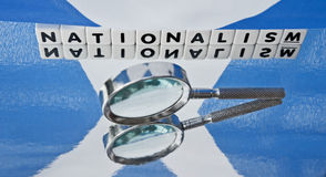 Studying Scottish Nationalism. Text 'nationalism' inscribed in uppercase letters on small white cubes with hand magnifier and Scottish flag or Saltire, concept Royalty Free Stock Image
