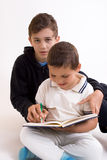 Studying siblings. A portrait of two siblings with elder brother helping his younger brother with his studies Royalty Free Stock Image