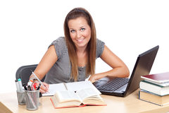 Studying with smile. Girl at table, studying and smiling Royalty Free Stock Photo