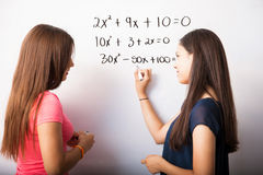 Studying some algebra. Cute young high school students solving some algebra equations on a white board royalty free stock photo