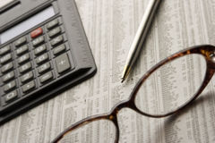 Studying the stock market. Paper, glasses, pen, and calculator, items showing someone looking over stocks Royalty Free Stock Photo