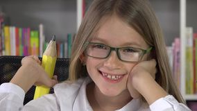 Studying student child smiling at camera in library, school girl portrait 4K.  stock video footage