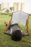 Studying. Teenage boy reading book in the garden Stock Photography