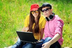 Studying together. Couple of modern teenagers sitting with a laptop outdoors Stock Photography