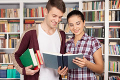 Studying together is fun. Cheerful young women and men standing close to each other and reading book at the library Stock Photo
