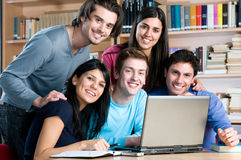Studying together at laptop. Happy smiling group of friends studying together at college library Royalty Free Stock Photography