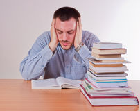 Studying very hard. Young man studying very hard with stack of books on his table Royalty Free Stock Images