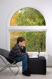 Studying by the window. Teen male working with a notebook computer with fall foliage visible through a large window Stock Photography